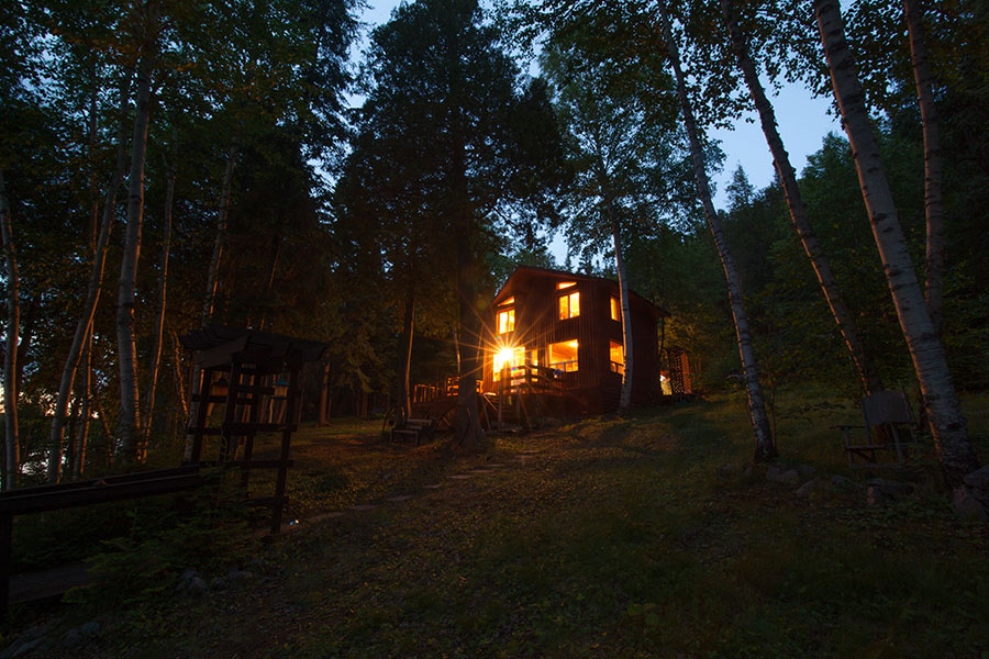 Cabin in the woods at night with lights on